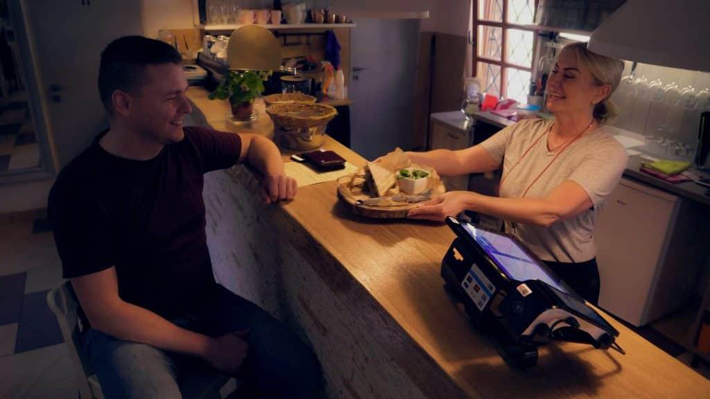 čašníčka podáva zákazníkovi jedlo v reštaurácií